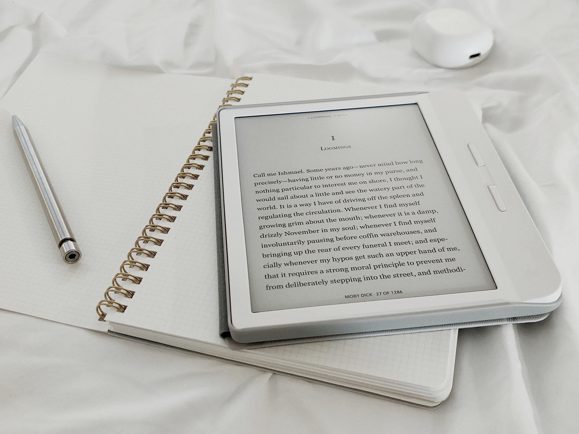 liseuse affichant un e-book, crayon et cahier